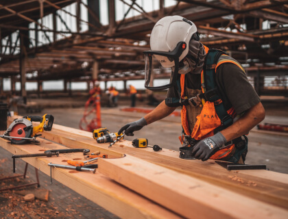 Man sawing wood at a construction site