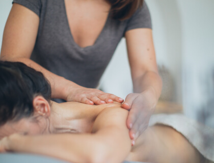 Physical therapy aide massaging a patient